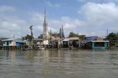 Häuser auf Stelzen am Ufer des Mekongs